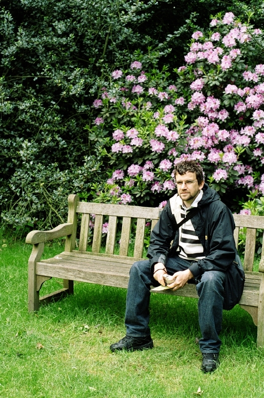 Andy relaxing in front of a rhododendron.