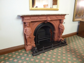 Odd fireplace - looks terracotta but its shiny. Is it painted or waxed? What the heck is it?