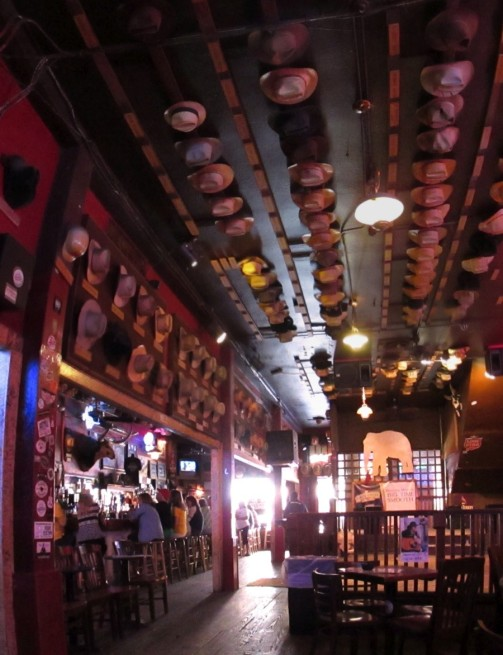 The interior of the bar is decorated with hats, each labeled with the owner's name