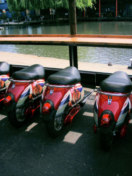 the seats in the eating area around the food stalls look like mopeds